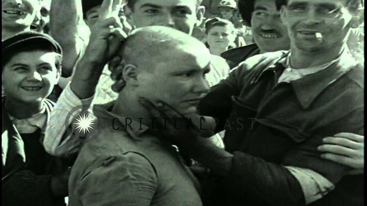 a woman collaborator with shaved head marched after the liberation