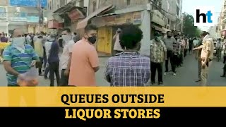Man showers flower petals on people queuing up at liquor s..