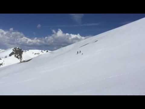 Skiers skiing down Handies Peak