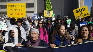 Demonstrators march in Dallas to mark the 50th anniversary of the filing of Roe v. Wade