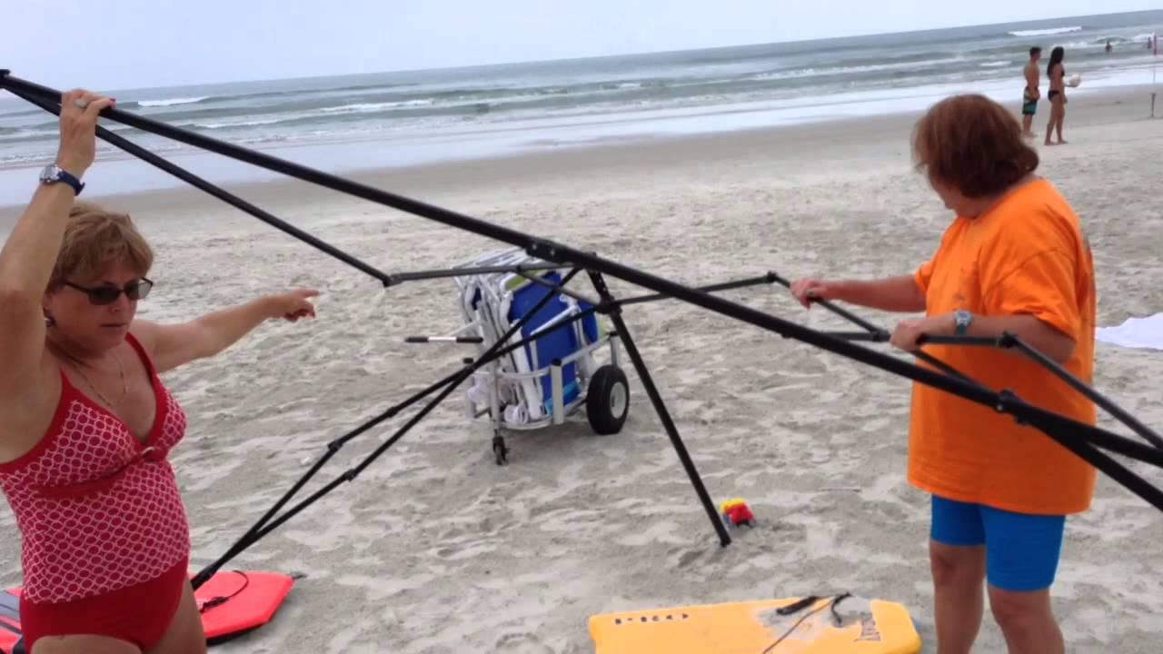 Deux femmes essaient de voler une tonnelle sur la plage