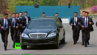 Men in Black: Kim's bodyguards run by his limo during summit