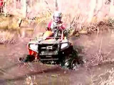 Polaris Sportsman 500 digging through the swamp with outlaws