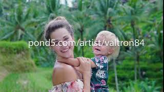 beautiful young mother with a child of 2 years in her arms looking at the camera and smiling against