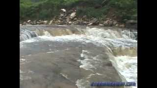 Sudden flash flood wave fills a creek bank-to-bank in seconds - multiple camera angles