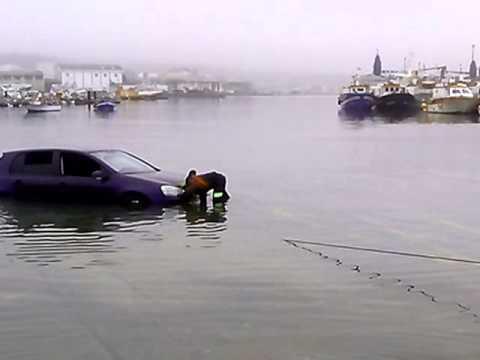 La marea atrapa un coche en la rampa del muelle de Riveira
