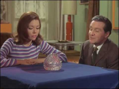 Youtube video - Emma and Steed gaze into a crystal ball, she sees a sign that says 'Tune in again next week' while he sees something more salacious