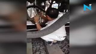 Chilling: Train moves as engineer fixes pipe under the tra..
