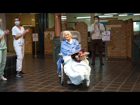 Hospital staff applaud a 100-year-old patient cured of COVID-19 | AFP photo