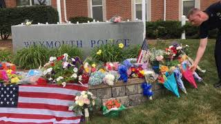 Little boy drops off flowers at makeshift memorial for Weymouth Police Officer Michael Chesna