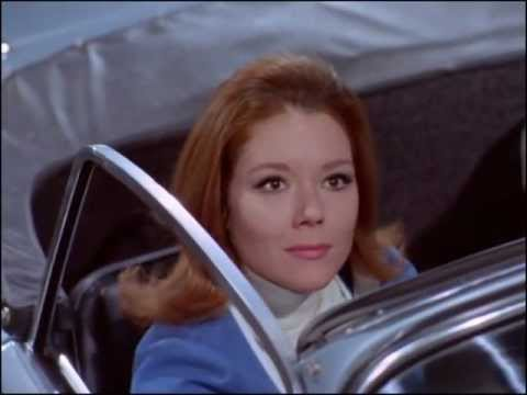 Youtube video - Mrs Peel is stopped at some traffic lights. When they turn amber, the light has 'MRS. PEEL' taped on it and the go light reveals 'WE'RE NEEDED'. She turns to find Steed in his Bentley behind her, doffing his hat